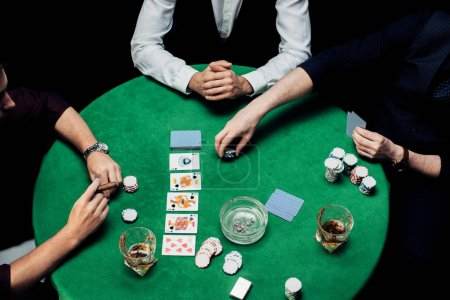 Photo pour Kyiv, Ukraine - 20 août 2019 : top view of men playing poker on poker table isolated on black - image libre de droit
