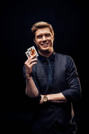 Photo pour Kyiv, Ukraine - 20 août 2019 : happy man holding playing cards isolated on black - image libre de droit