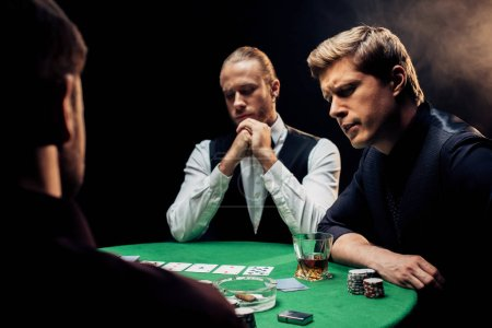 Photo pour Vue arrière de l'homme près du joueur et du croupier sur noir avec de la fumée - image libre de droit