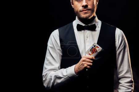 Photo pour Kyiv, Ukraine - August 20, 2019 : cropped view bearded croupier holding playing cards isolated on black - image libre de droit