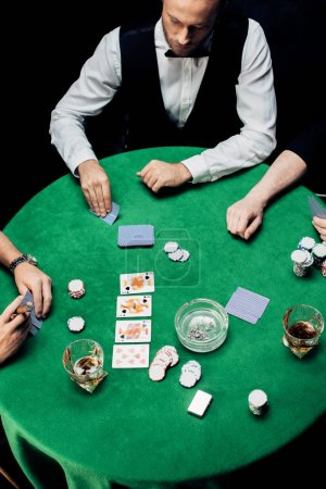 Photo pour Kyiv, Ukraine - 20 août 2019 : top view of men playing poker near croupier isolated on black - image libre de droit