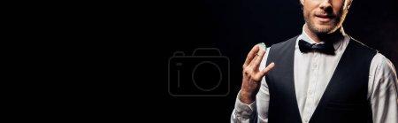 Photo pour Tir panoramique de l'homme barbu retenant la puce de poker d'isolement sur le noir - image libre de droit