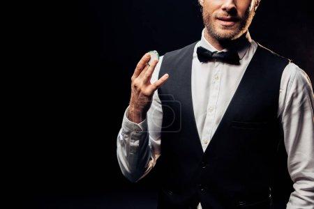 Photo pour Vue recadrée de l'homme dans l'usure formelle retenant la puce de poker d'isolement sur le noir - image libre de droit