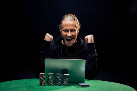 Photo pour Kyiv, Ukraine - 20 août 2019 : happy man gesturing while using laptop near poker chips isolated on black - image libre de droit
