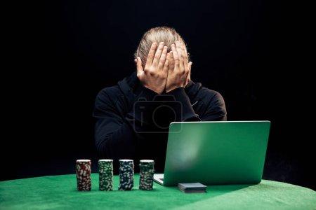 Foto de Kyiv, Ucrania - 20 de agosto de 2019: el hombre cubriendo la cara mientras utiliza laptop cerca de fichas de póquer aislados en negro. - Imagen libre de derechos