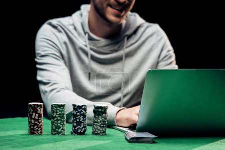 Photo pour Kyiv, Ukraine - August 20, 2019 : cropped view of happy man using laptop near poker chips isolated on black - image libre de droit