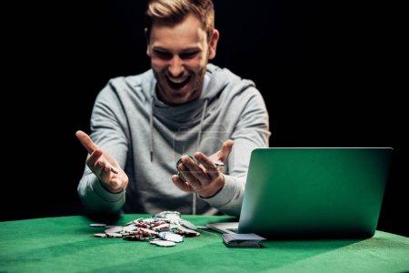 Photo pour Kyiv, Ukraine - August 20, 2019 : selective focus of happy man looking at poker chips near laptop isolated on black - image libre de droit
