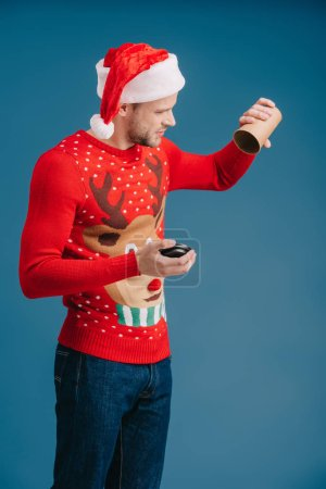 man in santa hat and christmas sweater holding empty cup of coffee, isolated on blue