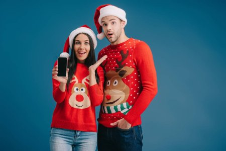surprised couple in santa hats and christmas sweaters showing smartphone with blank screen isolated on blue