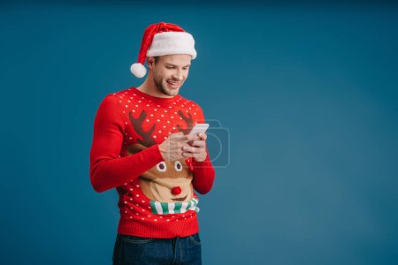 Photo for Smiling man in santa hat and christmas sweater using smartphone, isolated on blue - Royalty Free Image
