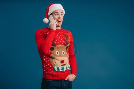 excited man in santa hat and christmas sweater talking on smartphone, isolated on blue