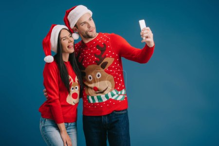 Photo for Couple in santa hats and christmas sweaters sticking tongues out while taking selfie on smartphone isolated on blue - Royalty Free Image