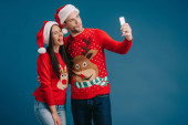 couple in santa hats and christmas sweaters sticking tongues out while taking selfie on smartphone isolated on blue