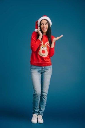 Photo pour Femme heureuse en santa chapeau et pull de Noël parler sur smartphone isolé sur bleu - image libre de droit
