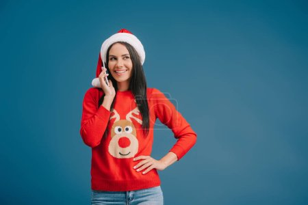 attractive woman in santa hat talking on smartphone isolated on blue