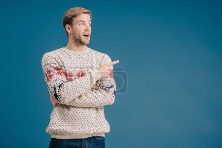 Photo pour Homme choqué en pull d'hiver montrant quelque chose isolé sur bleu - image libre de droit