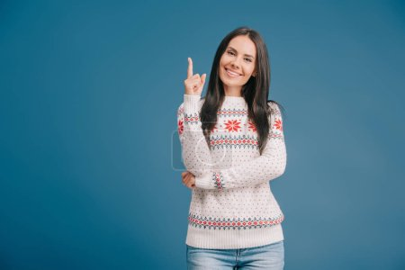 Photo for Cheerful woman in winter sweater pointing at something isolated on blue - Royalty Free Image