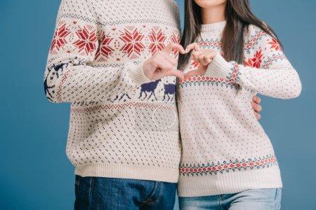 Photo pour Vue recadrée de couples dans des chandails d'hiver affichant le signe de coeur isolé sur le bleu - image libre de droit