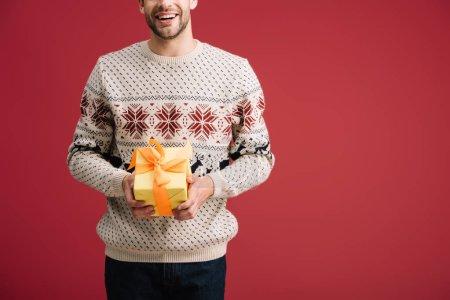 Foto de Recortado vista de sonriente hombre sosteniendo regalo aislado en rojo - Imagen libre de derechos