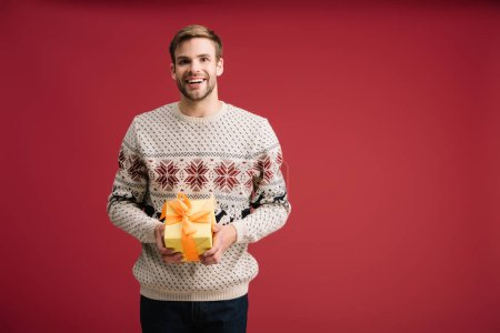 handsome smiling man holding christmas gift isolated on red