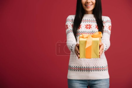 cropped view of beautiful woman holding christmas gift isolated on red
