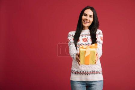 Photo pour Belle femme souriante tenant cadeau de Noël isolé sur rouge - image libre de droit