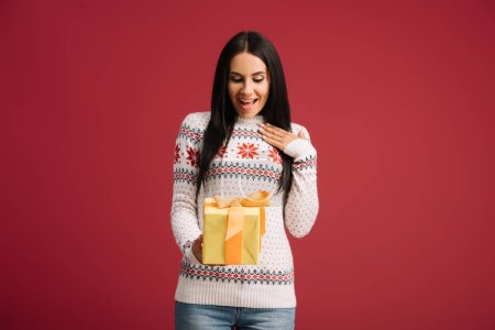 surprised girl holding christmas gift isolated on red