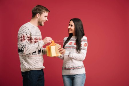 happy couple with christmas present isolated on red