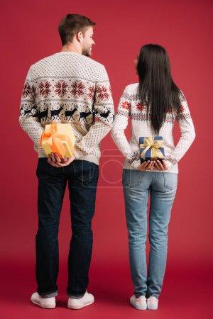 Photo pour Vue arrière de couples cachant des cadeaux de Noel d'isolement sur le rouge - image libre de droit