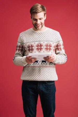 Photo pour Bel homme souriant en pull d'hiver en utilisant une tablette numérique isolée sur rouge - image libre de droit