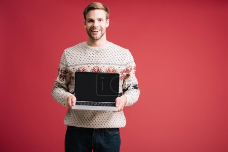 handsome smiling man showing laptop with blank screen isolated on red