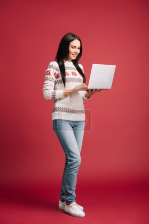 smiling woman in winter sweater using laptop isolated on red