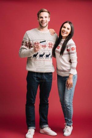 Photo pour Couples heureux dans des chandails d'hiver retenant la carte de crédit pour l'achats isolés sur le rouge - image libre de droit