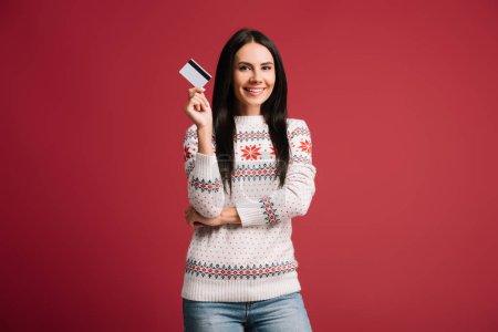 Photo pour Femme de sourire dans le chandail d'hiver retenant la carte de crédit, d'isolement sur le rouge - image libre de droit