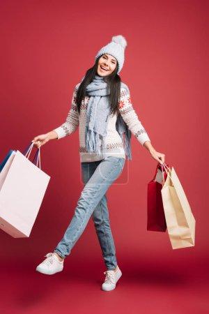 Photo pour Belle fille en pull d'hiver, écharpe et chapeau tenant des sacs à provisions, isolé sur rouge - image libre de droit