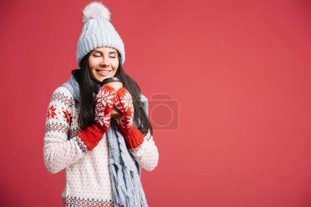 Photo pour Femme heureux dans le chapeau d'hiver, l'écharpe et les mitaines retenant le café pour aller, d'isolement sur le rouge - image libre de droit