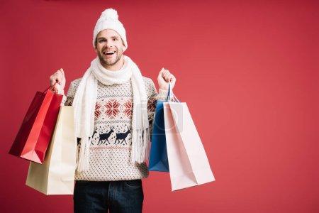Photo pour Bel homme souriant en vêtements d'hiver tenant des sacs à provisions, isolé sur rouge - image libre de droit