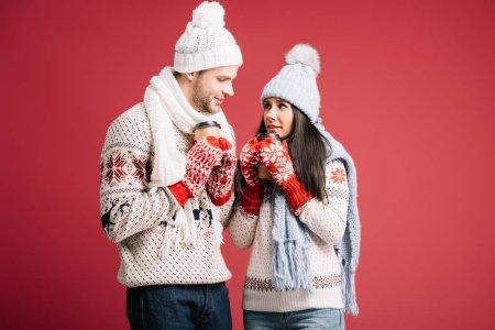 Photo pour Couples heureux dans des chandails, des chapeaux, des écharpes et des mitaines retenant le café pour aller isolé sur le bleu - image libre de droit