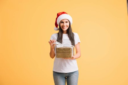 Photo for Beautiful woman in santa hat holding christmas gift box isolated on yellow - Royalty Free Image