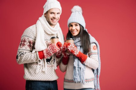 Photo for Smiling couple in sweaters, hats, scarves and mittens holding coffee to go isolated on blue - Royalty Free Image