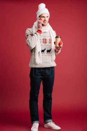 Photo pour Bel homme dans le chandail d'hiver, l'écharpe, le chapeau et les mitaines retenant le café pour aller tout en parlant sur le smartphone, d'isolement sur le rouge - image libre de droit