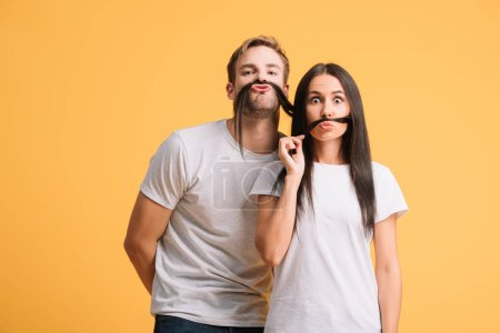 Photo for Funny couple in white t-shirts making mustache from hair, isolated on yellow - Royalty Free Image