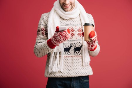Photo for Cropped view of man in winter sweater, scarf, hat and mittens holding coffee to go while using smartphone, isolated on red - Royalty Free Image