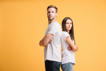 offended couple standing with crossed arms, isolated on yellow