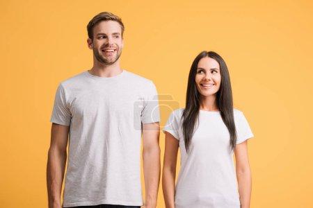 Photo pour Beau couple joyeux posant en t-shirts blancs, isolé sur jaune - image libre de droit