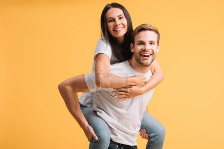 Photo for Beautiful happy couple piggybacking in white t-shirts, isolated on yellow - Royalty Free Image