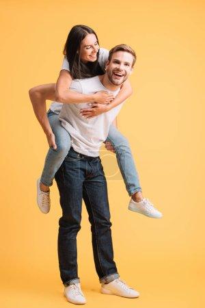 Photo pour Homme heureux piggybacking sa petite amie, d'isolement sur le jaune - image libre de droit