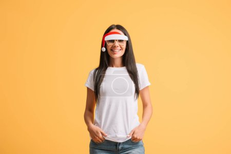 attractive woman in white t-shirt and glasses with santa hat isolated on yellow