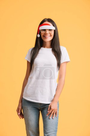 Photo for Beautiful smiling woman in white t-shirt and glasses with santa hat isolated on yellow - Royalty Free Image