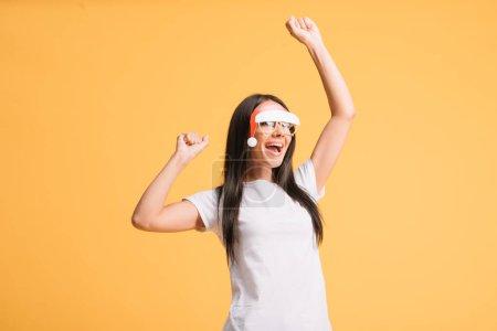 Photo pour Danse heureuse de fille dans des glaces avec le chapeau de santa d'isolement sur le jaune - image libre de droit